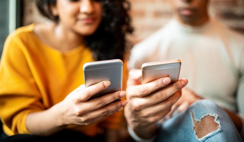 Amigos enviando dinero entre sí por teléfono móvil