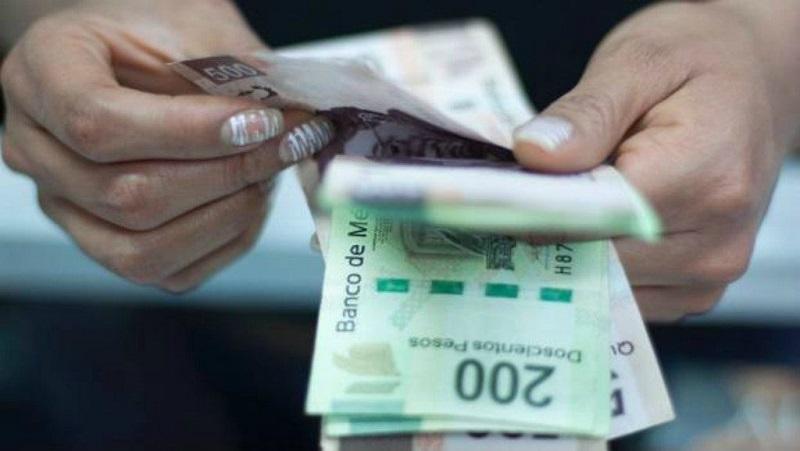 Persona contando pesos mexicanos