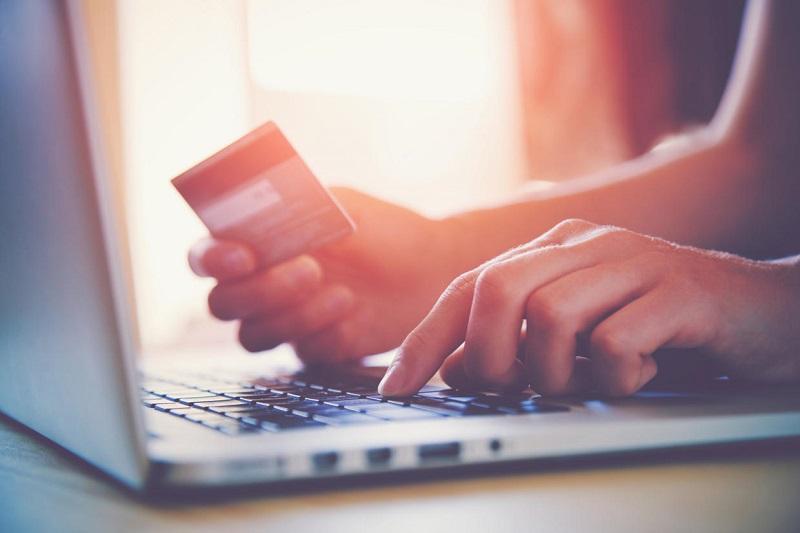 Persona con tarjeta de crédito y computadora